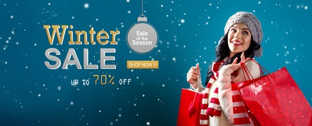 Winter sale message with young woman holding shopping bags Stock Photo