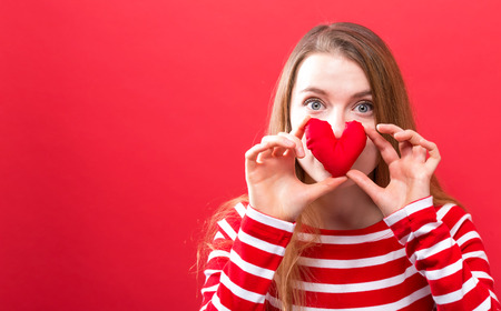 Happy young woman holding a heart cushion on a red background Фото со стока