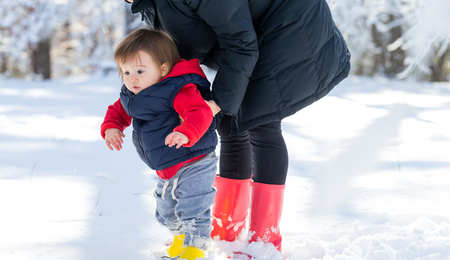 Toddler boy playing in the snow with his mother Фото со стока