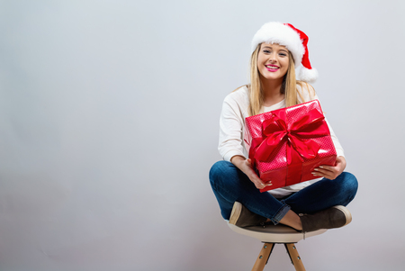 Young woman with santa hat holding a gift box on a gray background Фото со стока