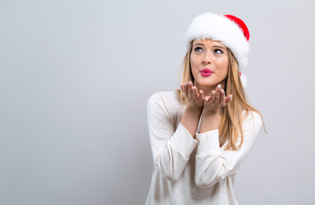 Happy young woman with Santa hat blowing a kiss on a gray background