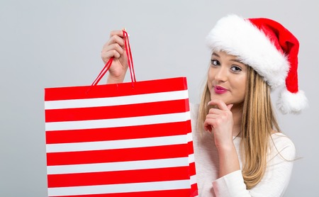 Young woman with santa hat holding a shopping bag on a gray background Фото со стока