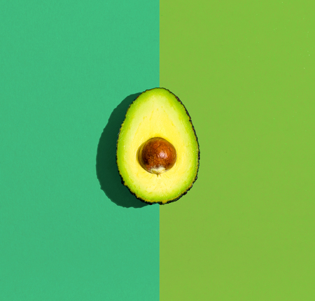 Fresh avocado on a green background flat lay