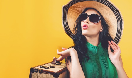 Young woman with a suitcase travel theme on a yellow background Фото со стока