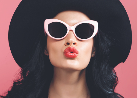 Fashionable woman in sunglasses on a pink background