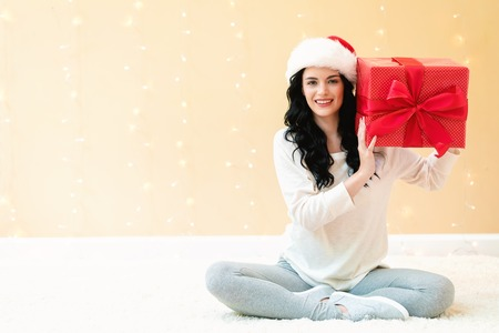 Young woman with santa hat holding a gift box on a shiny light background