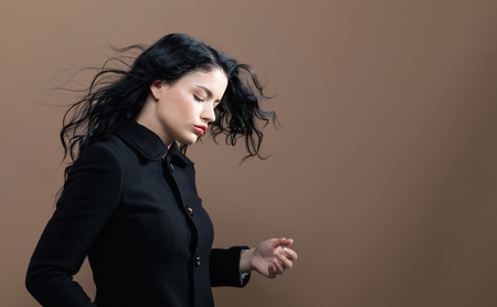 Beautiful young woman in a fashionable coat on a brown background