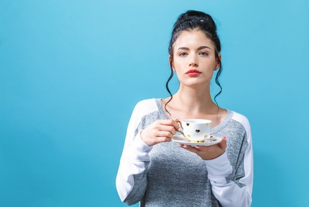 Young woman drinking coffee on a solid background