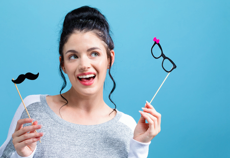 Young woman holding paper glasses and mustache party sticks on a blue background Фото со стока