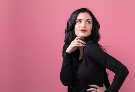 Beautiful young woman on a pink background Фото со стока