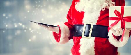 Santa holding a tablet computer on a shiny light background Фото со стока