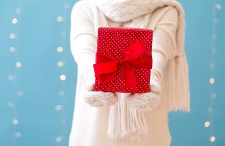 Woman holding a Christmas gift box on a shiny light blue background Фото со стока