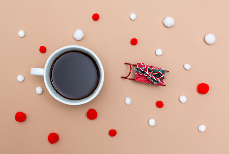 Cup of coffee with a miniature snow slide on a light brown paper background