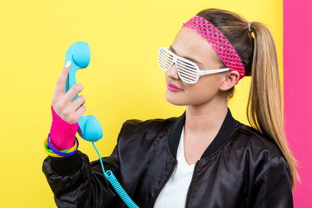 Woman in 1980s fashion with old fashioned phone on a split yellow and pink background Banque d'images - 110814576
