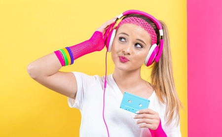 Woman in 1980s fashion holding a cassette tape on a split yellow and pink background Фото со стока