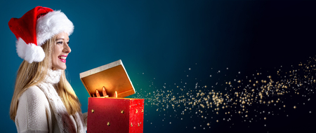 Happy young woman with Santa hat opening a gift box