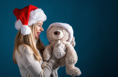 Young woman with santa hat holding a teddy bear on a dark blue background Фото со стока