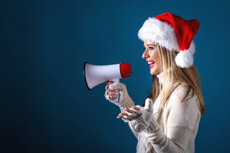 Young woman with santa hat holding a megaphone on a dark blue background