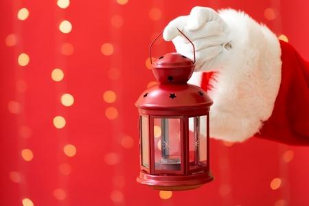 Santa holding a lantern on a shiny light red background