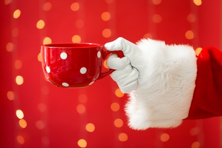 Santa holding a coffee cup on a shiny light red background