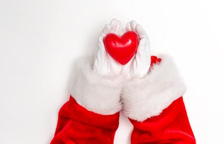 Santa holding a heart on a white background Фото со стока