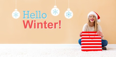 Hello winter message with happy woman with Santa hat holding a shopping bag Фото со стока