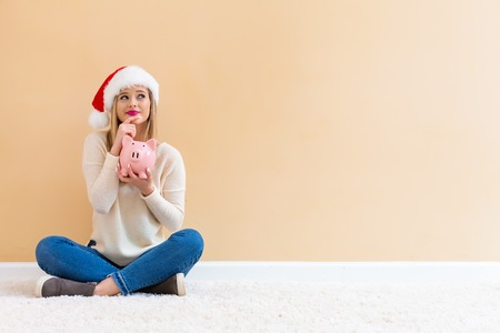 Young woman with santa hat holding a piggy bank on a white carpet Stock Photo