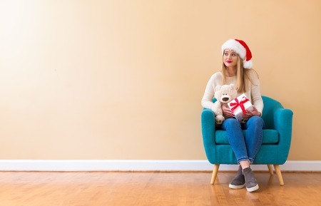 Young woman with santa hat holding a teddy bear in a chair