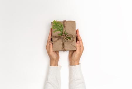 Person holding a Christmas gift box on a white background Фото со стока