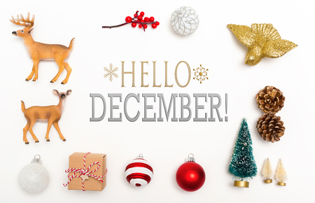 Hello December message with small Christmas ornaments on a white background