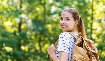 Young woman hiking from behind on a bright summer day in the forest