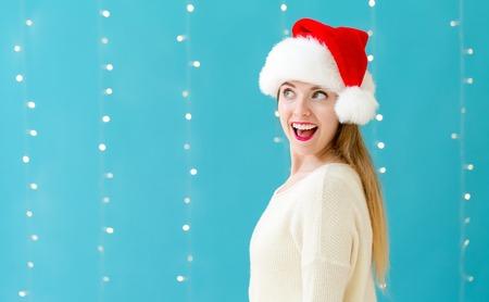 Happy woman with a Santa hat on a shiny light background Фото со стока