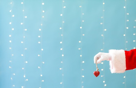 Santa holding a Christmas heart on a shiny light blue background