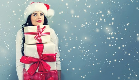 Young woman with santa hat holding gift boxes on a gray background Stock Photo