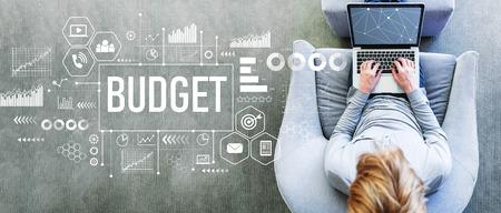 Budget mit Mann, der einen Laptop in einem modernen grauen Stuhl benutzt using