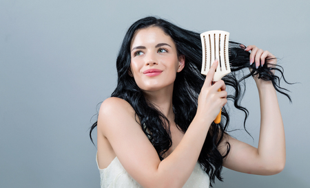 Beautiful young woman holding a hairbrush on a gray background Stockfoto - 111596196