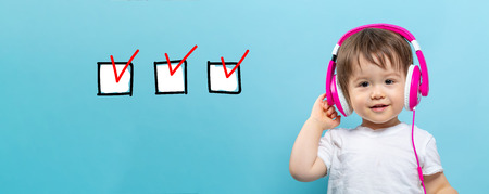 Checklist with toddler boy with headphones on a blue background Stock Photo