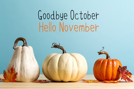 Goodbye October Hello November message with pumpkins on a blue background Stock Photo