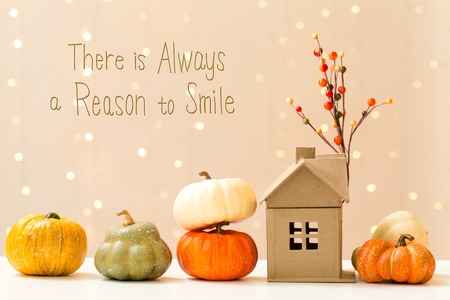 There is always a reason to smile message with collection of autumn pumpkins with a toy house Фото со стока