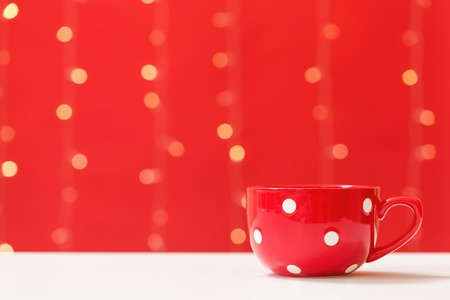 Cup of coffee on a shiny light red background