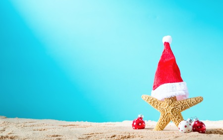 Starfish with santa hat with Christmas ornaments on a beach sand Stock Photo