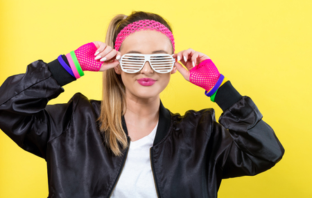 Woman in 1980s fashion with shatter shade glasses on a yellow background