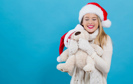 Young woman with santa hat holding a teddy bear on a blue background