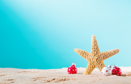 Starfish with Christmas ornaments on a beach sand