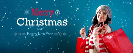 Mensaje de feliz Navidad y próspero año nuevo con mujer joven sosteniendo bolsas de la compra.