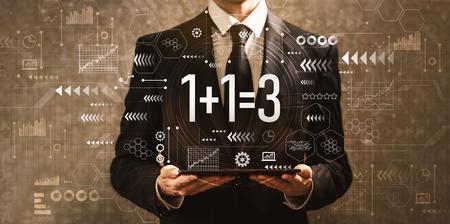 1 más 1 igual a 3 con el empresario sosteniendo una tableta sobre un fondo vintage oscuro