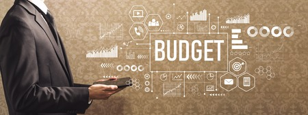 Budget with businessman holding a tablet computer on a dark vintage background Stockfoto