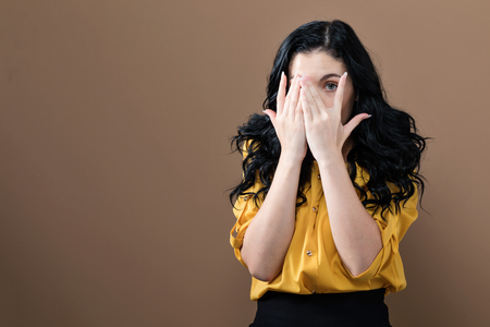 Young woman peeking though her fingers on a brown background