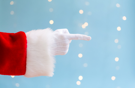 Santa with pointing gesture on a shiny light blue background