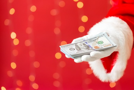 Santa holding US dollar bills on a shiny light red background